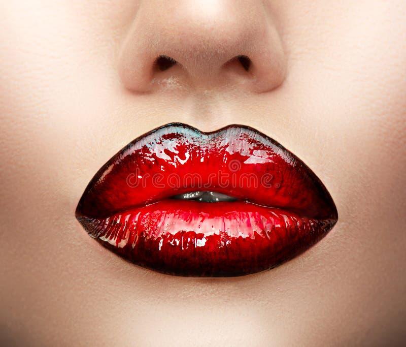 Lippenmake-up Schönheitshaute couture-Steigungslippenmake-upprobe, schwarz mit roter Farbe Sexy Mundnahaufnahme stockbilder