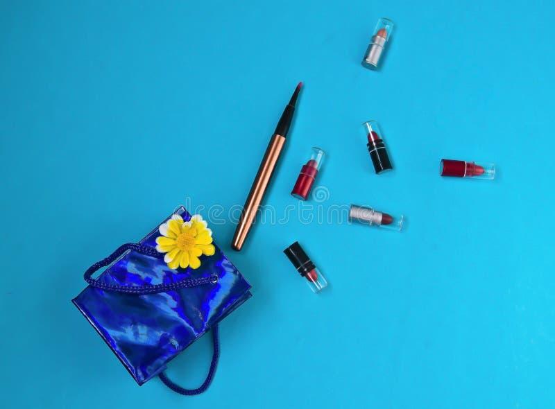 Lippenstift, borstel, pakket, gift, verrassing, op blauwe achtergrond stock foto