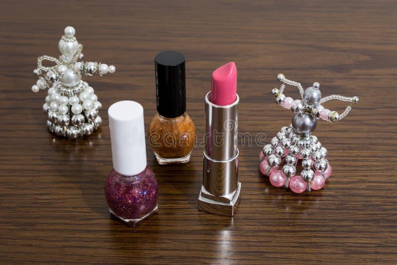 Lippenstift und Nagellacke verziert mit handgemachten Weihnachtsengeln auf Tabelle stockfoto