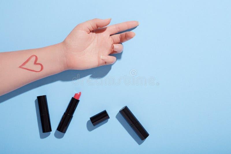 Lippenstiftschlagmanntest auf Frau ` s Hand, flache Lage, Tischplatteansicht, blauer Hintergrund lizenzfreie stockfotos