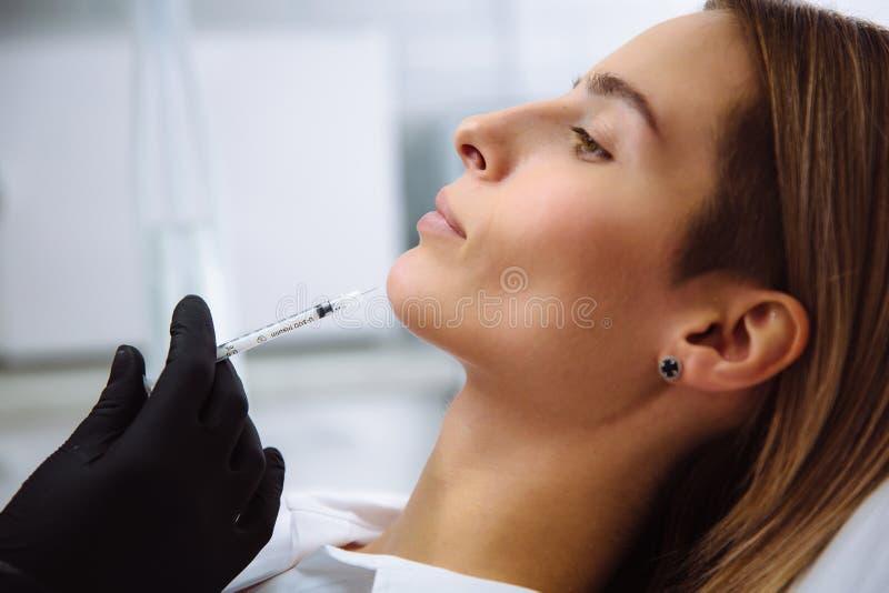 Lippenverhoging Close-up mooie vrouwelijke gezicht en cosmetologist` s handen met spuit tijdens gezichtsschoonheidsinjecties stock afbeelding