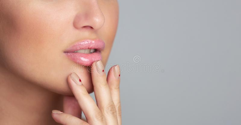 Lips care. Girl applying balm over grey background, closeup. Copy space, panorama royalty free stock photo