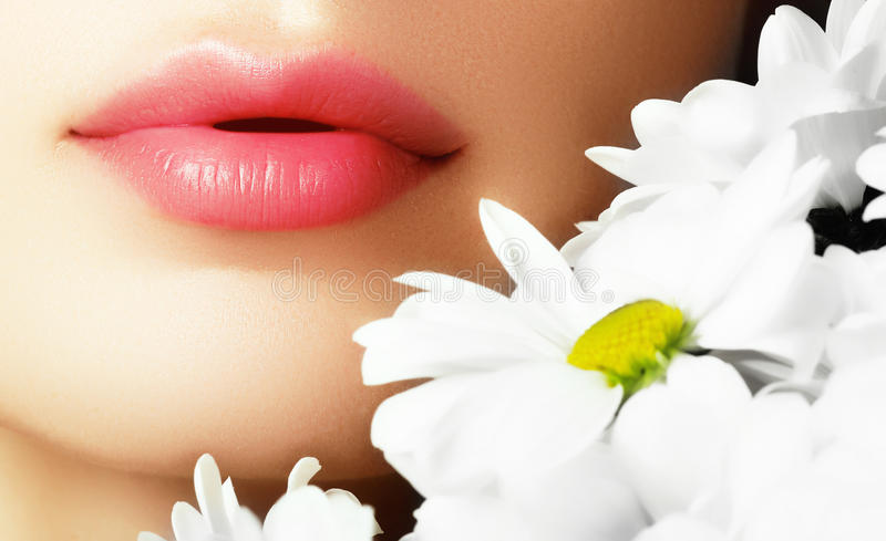 Lips with flower. Close-up beautiful female lips with bright lip stock photos