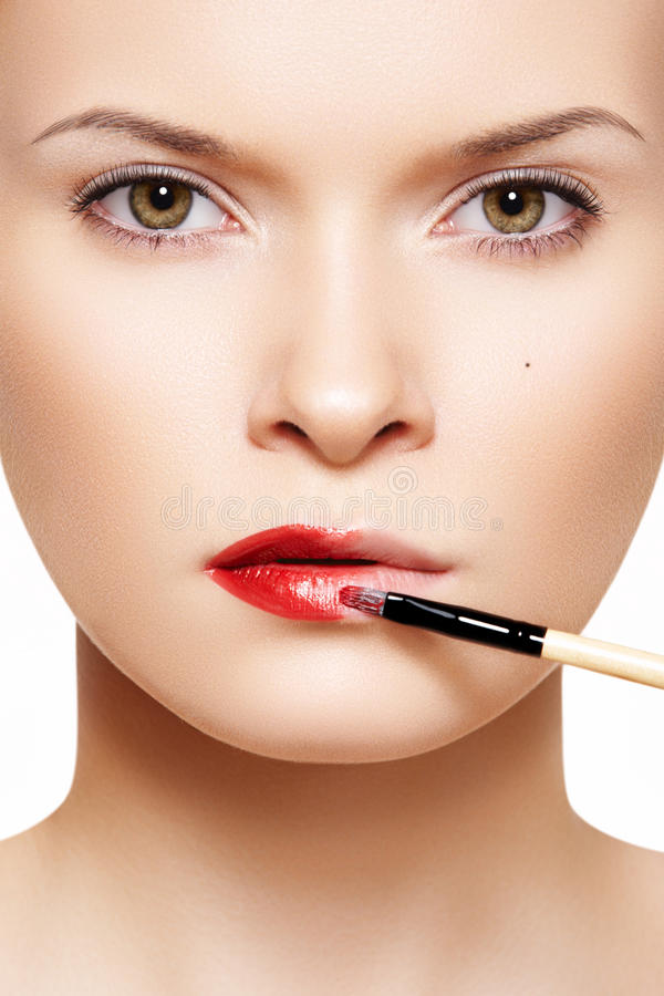 Lips make-up. Applyng red lipstick using lip brush stock image