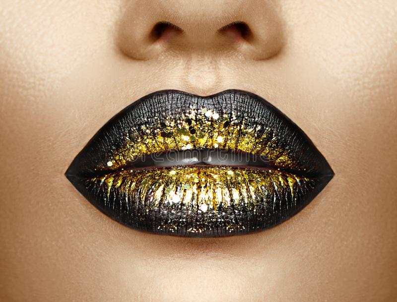 Lips makeup. Beauty high fashion gradient lips makeup sample, black with golden color. mouth. Lipstick stock photo