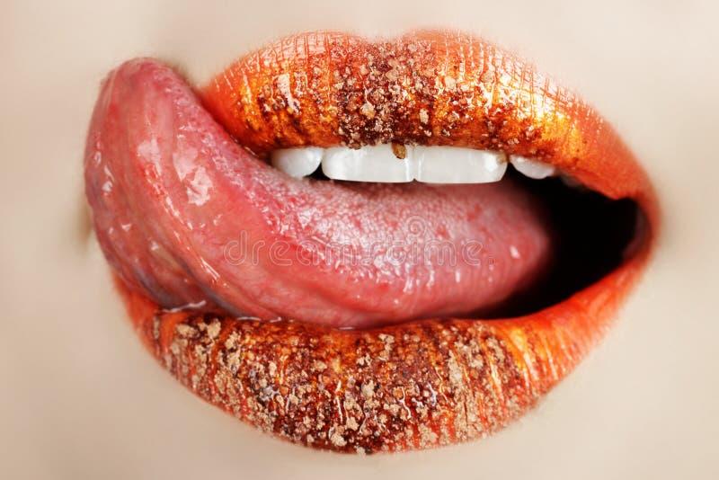 Lips and tongue macro. Macro of bright orange make-up on lips with tongue licking off chocolate powder royalty free stock photo