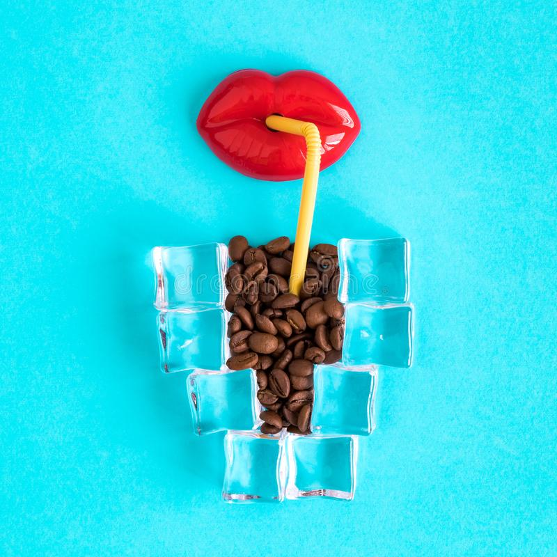 Lips toy with drinking straw and cup of ice coffee made of ice cubes and coffee beans stock image