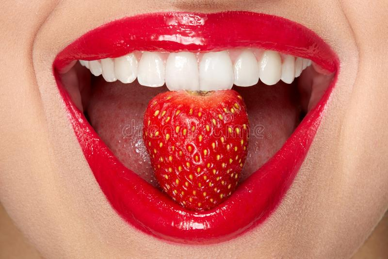 Lips. Woman With Red Lipstick And Strawberry. Close Up Of Plump Full Lips With Professional Lip Makeup Holding Berry In White Healthy Teeth. Beauty And royalty free stock images