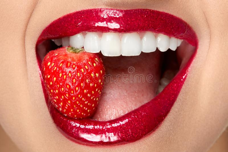 Lips. Woman With Red Lipstick And Strawberry. Close Up Of Plump Full Lips With Professional Lip Makeup Holding Berry In White Healthy Teeth. Beauty And stock image
