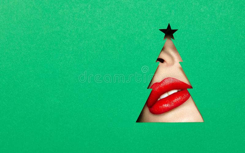 Lips of a young beautiful woman with a red lipstick. Beautiful Plump Bright Lips Of a Young Beautiful Woman with Red Lipstick Look Into the Pattern of Christmas stock image