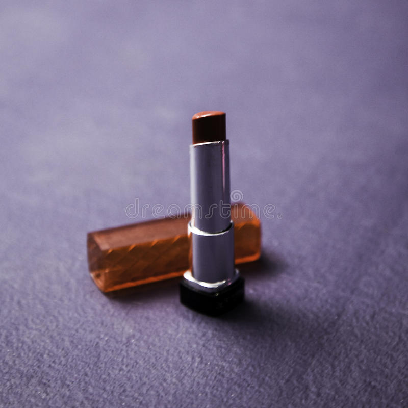 Lipstick. Red lipstick on purple background royalty free stock image