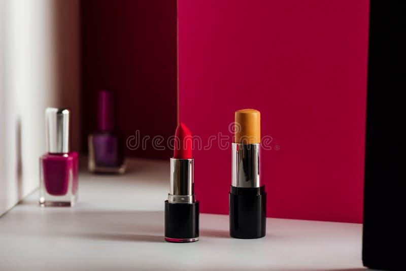 Lipstick, bar Concealer en zeefreefjes op een moderne roze achtergrond Product en cosmetica royalty-vrije stock foto