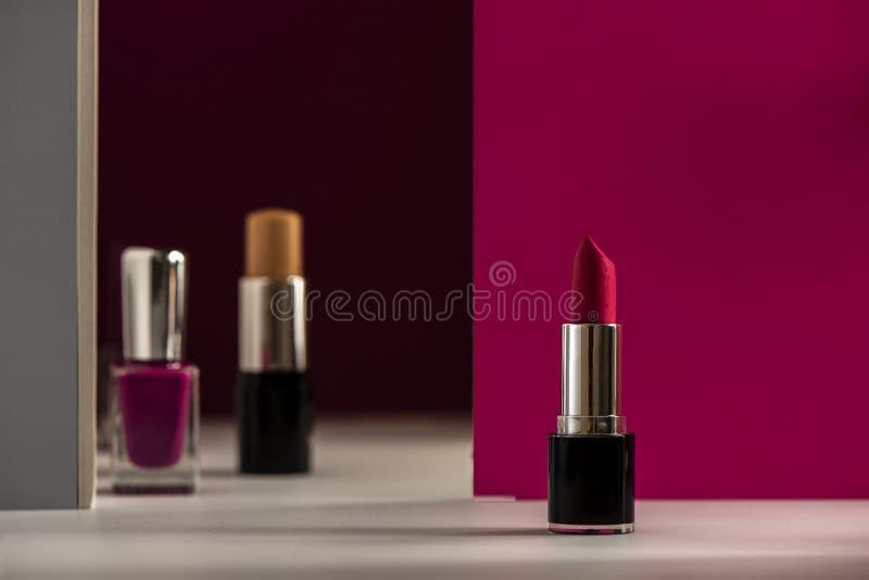 Lipstick, bar Concealer en zeefreefjes op een moderne roze achtergrond Product en cosmetica royalty-vrije stock foto's
