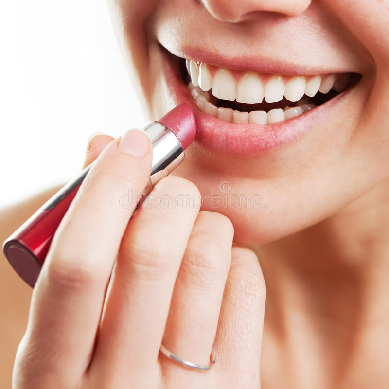 Lipstick and female lips. Lipstick and happy female lips over white stock image