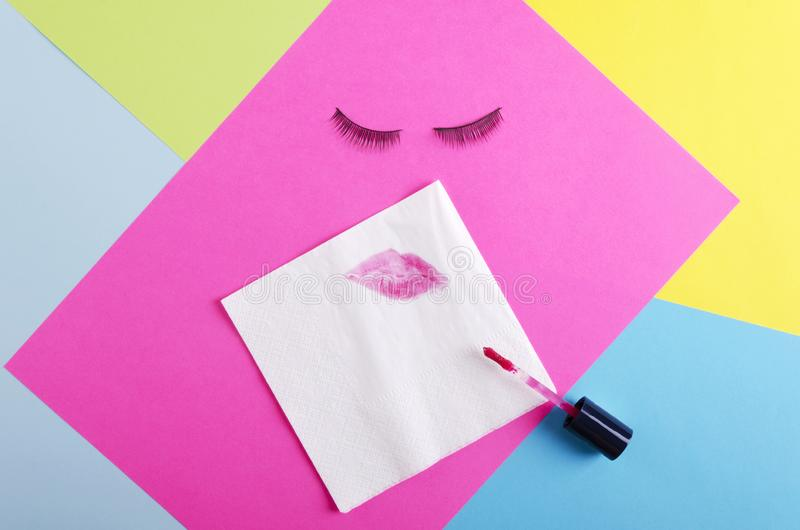 Lipstick kiss on the white napkin, false eyelashes on the colorful background.Abstract shape of female face royalty free stock images
