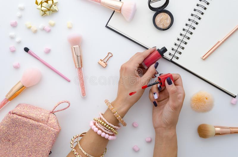 Lipstick makeup swatches on female hand,. Woman holding lipstick. Beauty blog flat lay with makeup accessories royalty free stock photo
