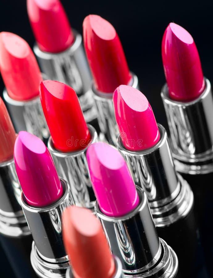 Lipstick. Professional makeup and beauty. Lipstick tints palette closeup. Colorful lipsticks over black stock photography