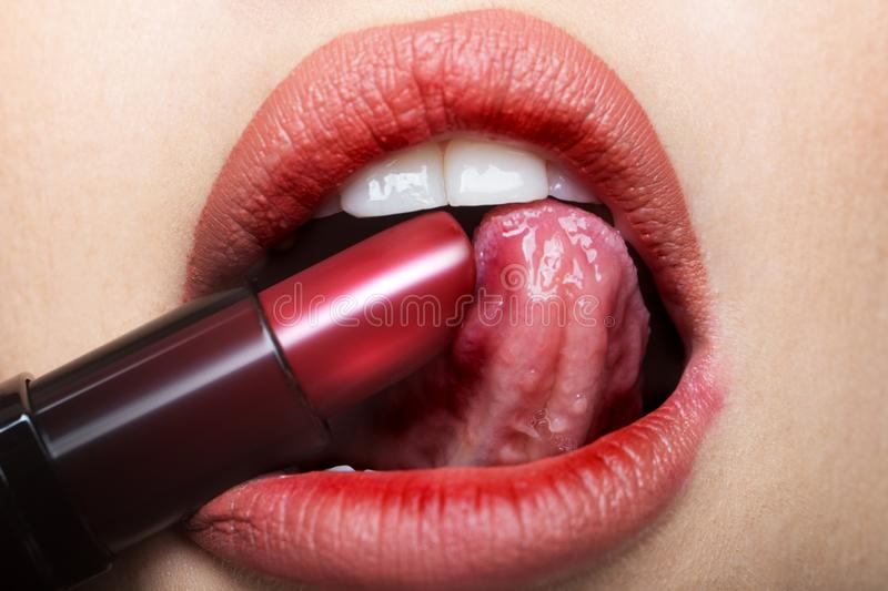 Lipstick, sexy tongue in female mouth. Red lips and open sensual mouth from young girl or woman. Exciting makeup for stock image