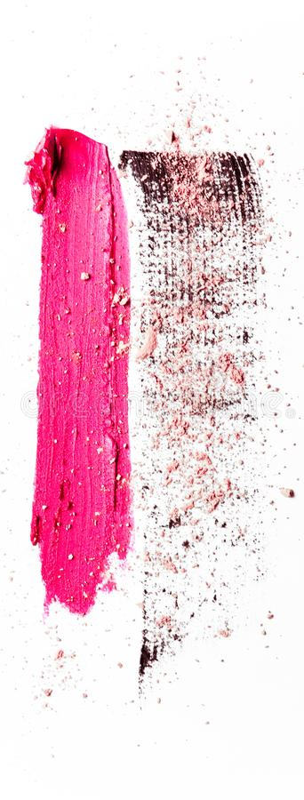 Lipstick smudge, mascara stroke and crushed eyeshadow isolated on white background. Beauty texture, cosmetic product and art of make-up concept - Lipstick smudge royalty free stock photography