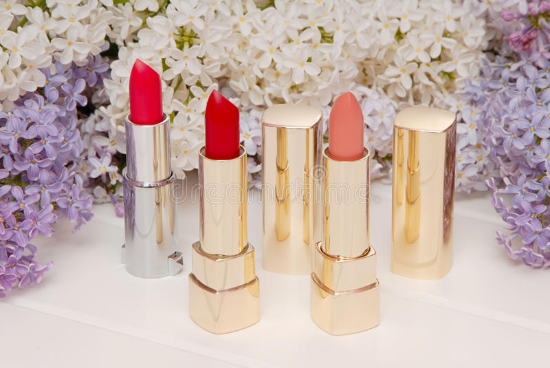 Lipsticks and blossoming lilac royalty free stock photos