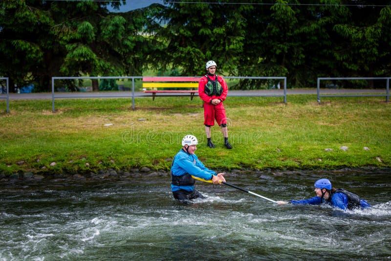 Liptovsky Mikulas/Словакия - 22-ое июня 2019: девушка будучи вытягиванным из воды путем сплавлять инструктор центра подготовки стоковые фото