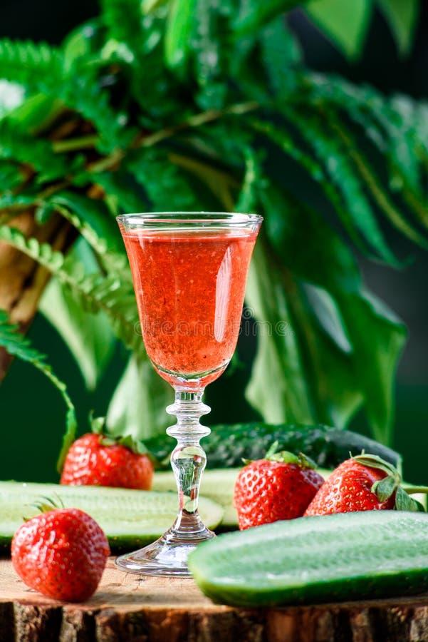 Liqueur de fraise et de concombre, sur le fond vert image libre de droits