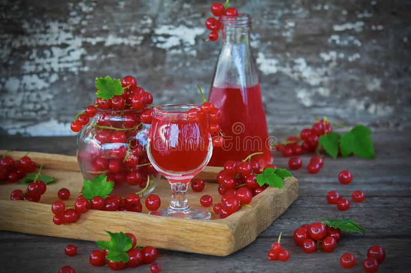 Liqueur of red currant in the glass. And fresh berries on the old background stock photography