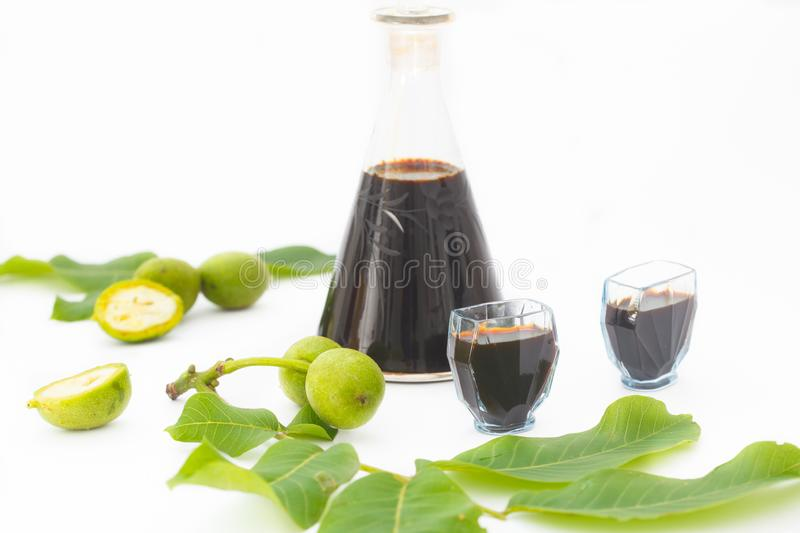 Liqueur from young green walnuts, remedy for stomach ache. Bottle with walnut spirit and two glasses on white background stock images