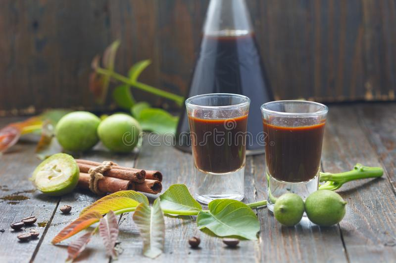 Liqueur from young green walnuts, remedy for stomach ache. Homemade walnut liquor stock photos