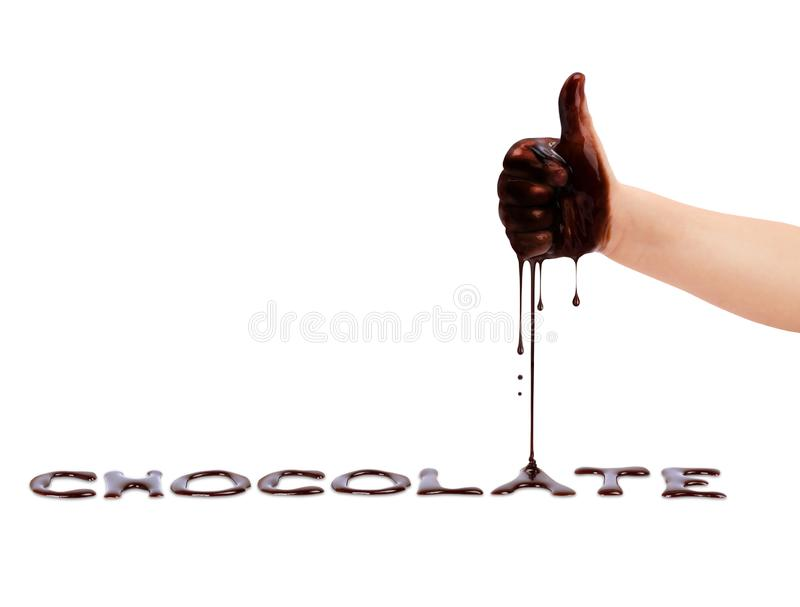 Liquid chocolate pours from child`s hand on a white background.  stock image