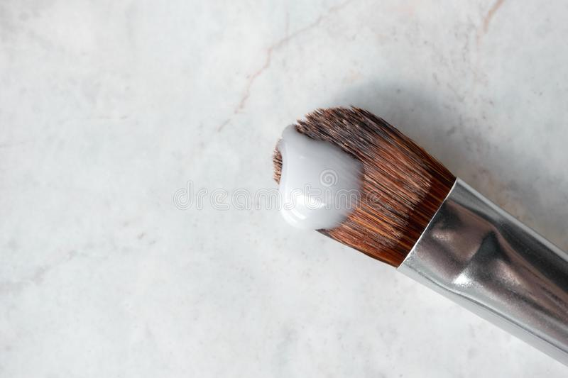 Liquid cosmetic brush cleaner on marble background. Care for makeup brushes royalty free stock photo