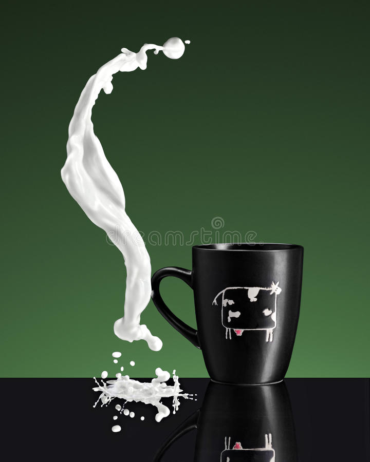 Liquid curved splash of milk near cup royalty free stock photography