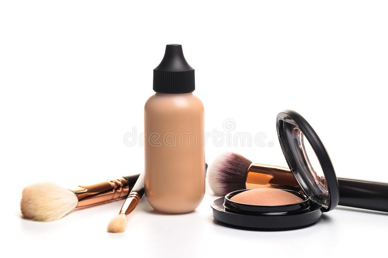 Liquid makeup foundation cream and  shadow, blush, powder, sculptor in a pack with make up brushes on a white background. Isolated royalty free stock images