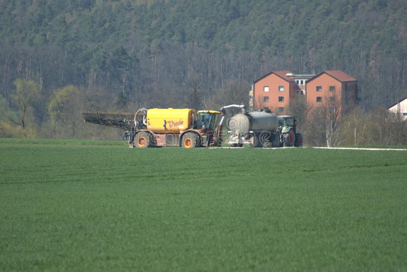 A liquid manure AKA slurry spreader being refilled royalty free stock image