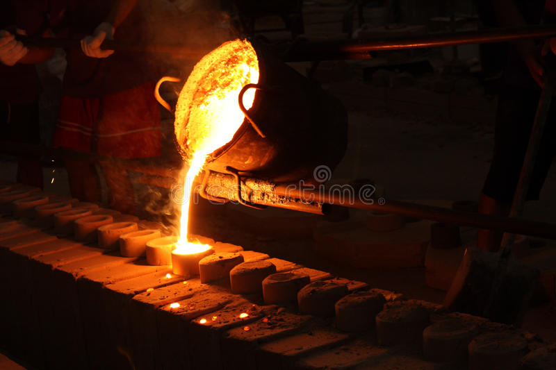 Liquid metal from casting ladle Ferrous metallurgy. Molten metal poured from ladle for casting stock photos