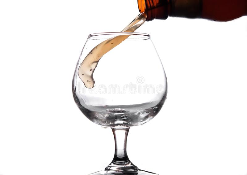 The liquid is poured into a glass and spray. The liquid is poured into a glass beaker and is sprayed onto a white background isolate royalty free stock photo
