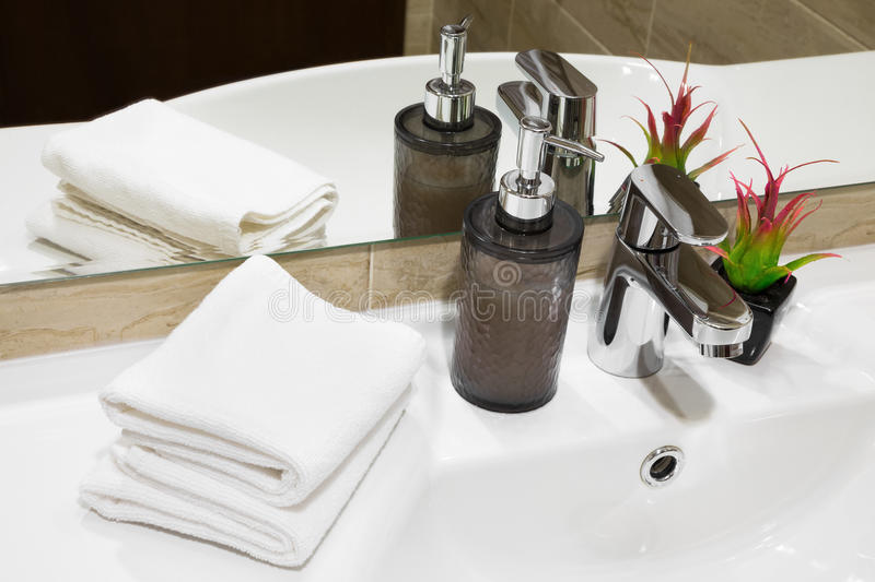 Liquid soap pump, towels and plant on a hand basin. Stylish liquid soap pump and potted flowering plant on a white hand basin with clean towels in a hotel or stock photo