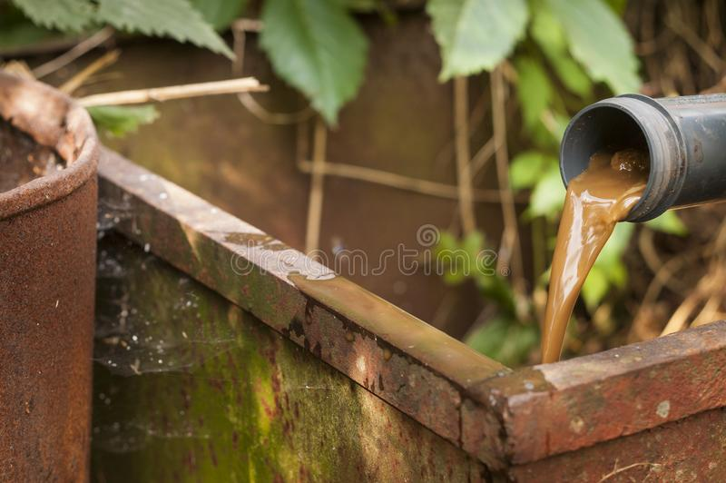 Liquid waste removal. Out of plastic pipe into a meatl box, outdoor closeup stock image