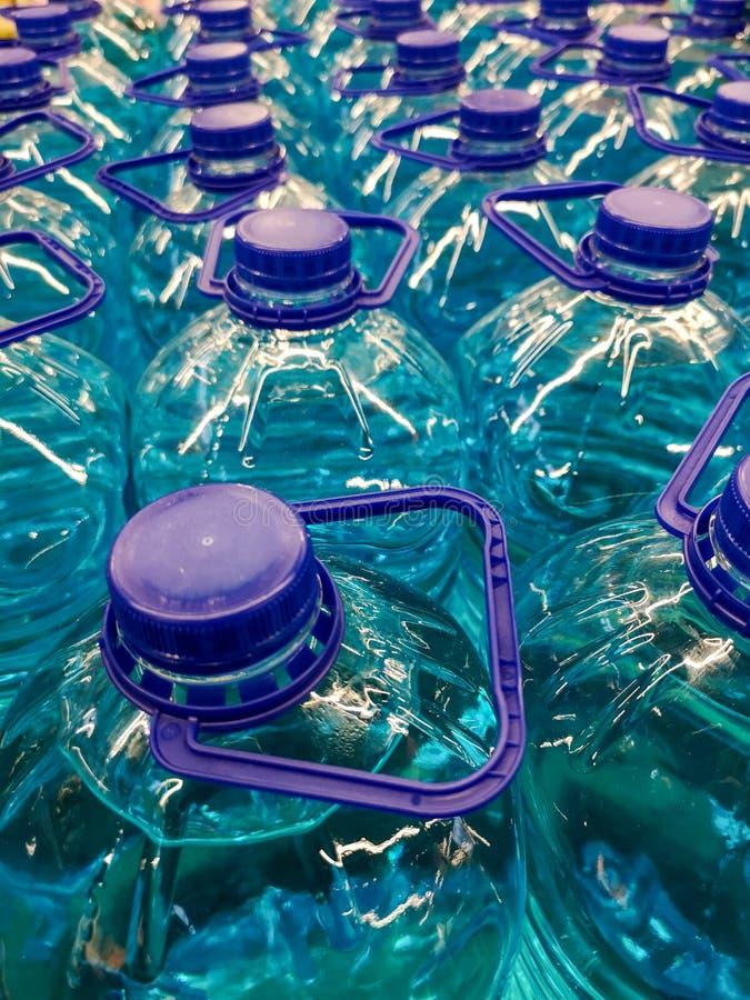 Liquide bleu dans des bouteilles en plastique comme fond photographie stock libre de droits