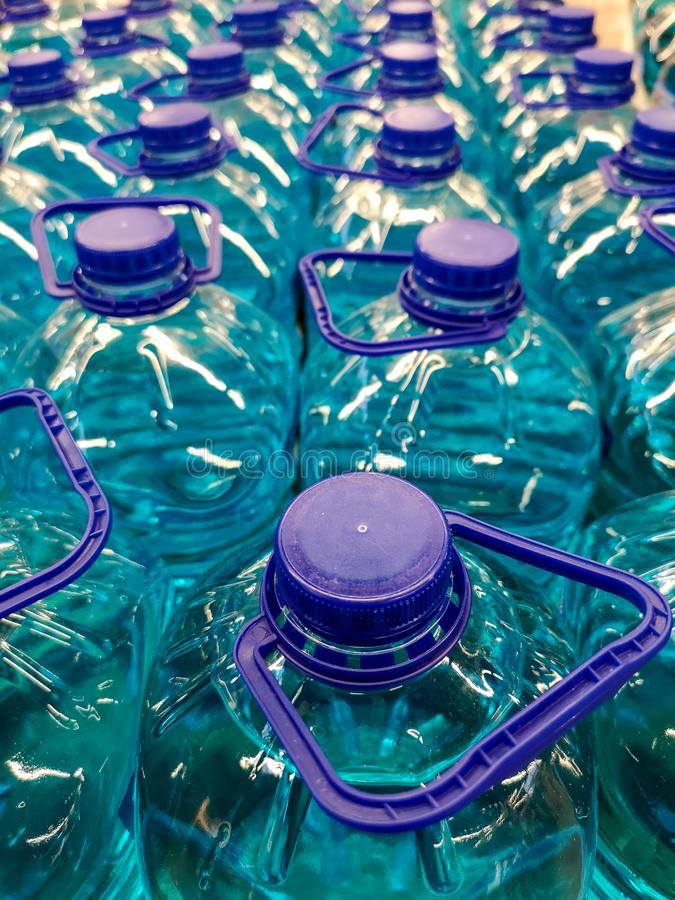 Liquide bleu dans des bouteilles en plastique comme fond photo stock