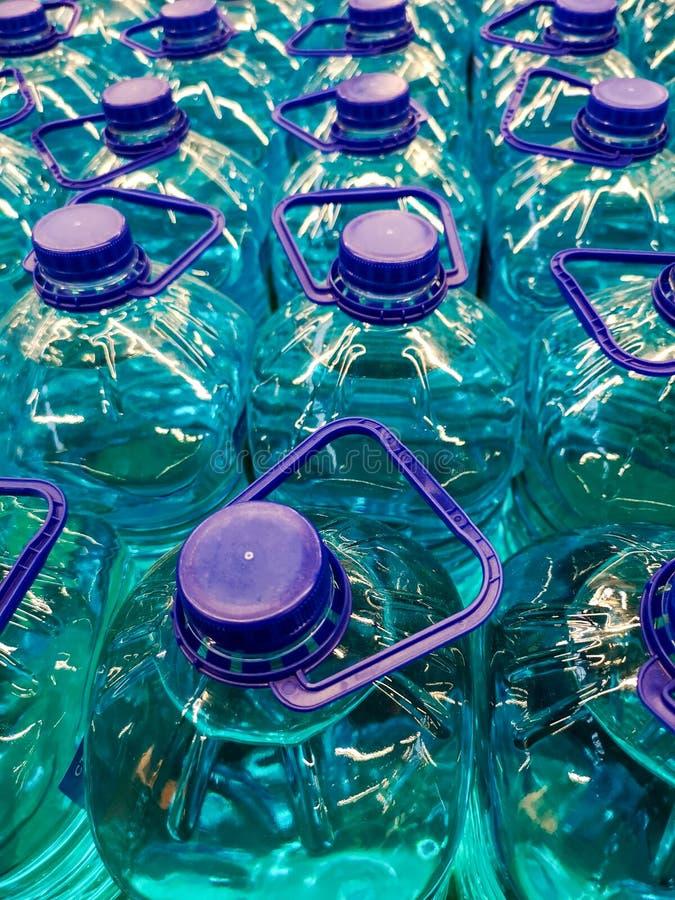 Liquide bleu dans des bouteilles en plastique comme fond photos stock