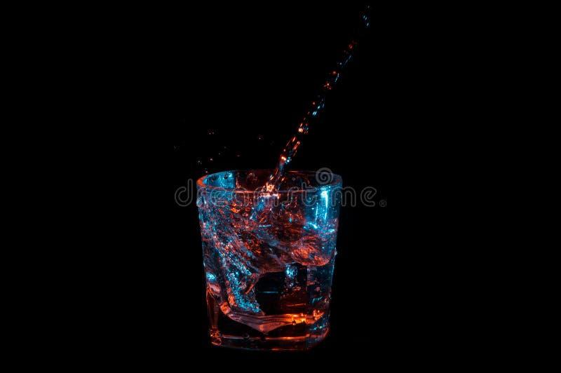Liquide clair étant versé dans une spirale dans lumières de roches bleu de dessous en verre et orange d'isolement sur un fond noi photo libre de droits