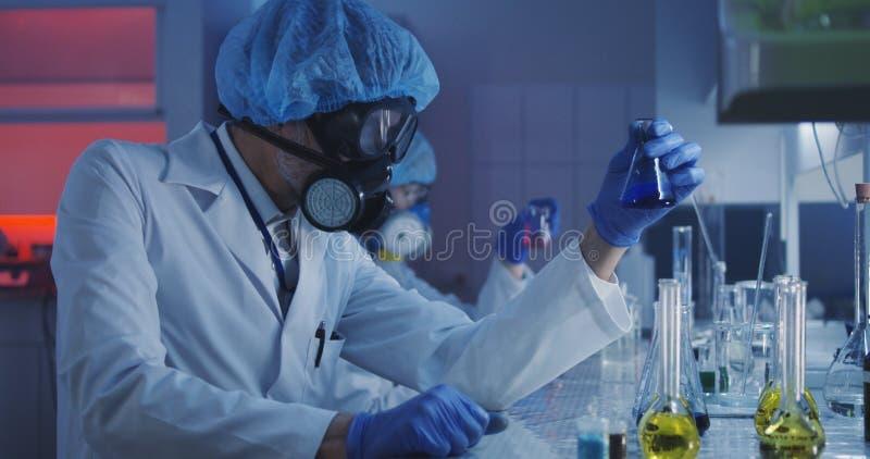 Liquide de versement de scientifique dans la fiole conique photographie stock libre de droits