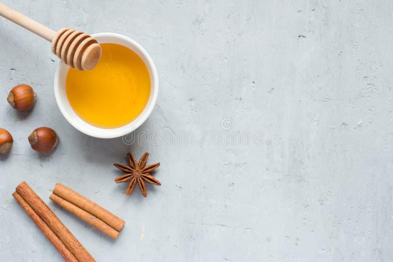 Liquide et anis de miel avec de la cannelle sur un fond clair copie photo libre de droits