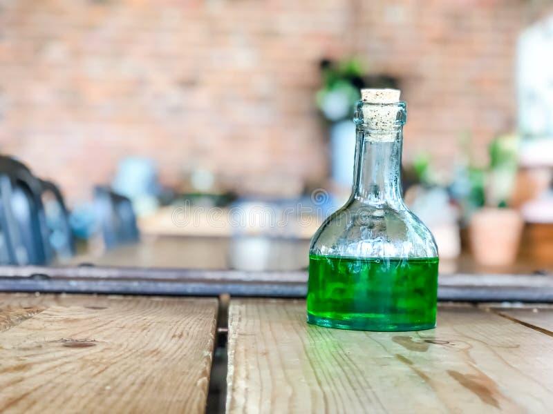 Liquide vert dans des bouteilles en verre sur la table en bois au café, boire de boisson photo stock