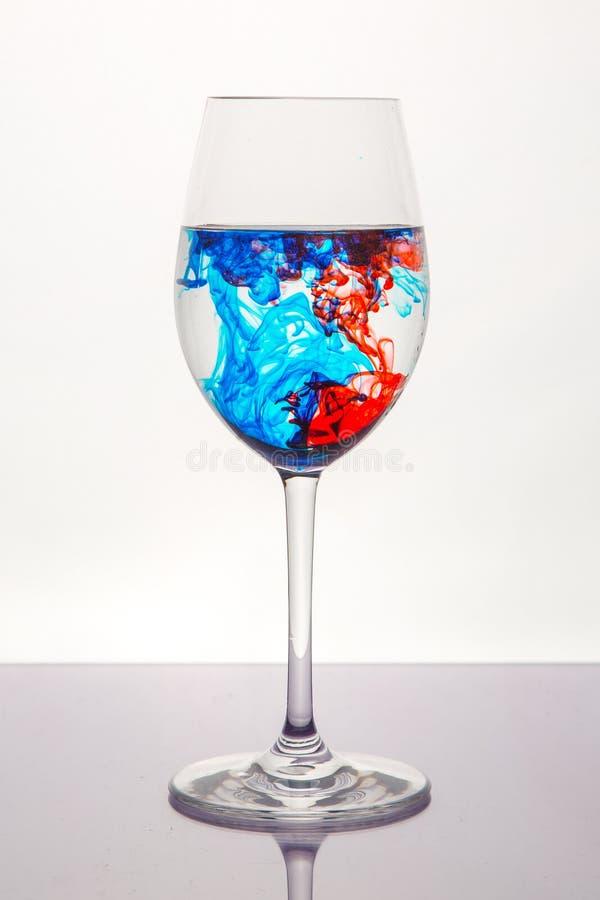 Liquido di rosso blu in vetro di vino immagine stock libera da diritti