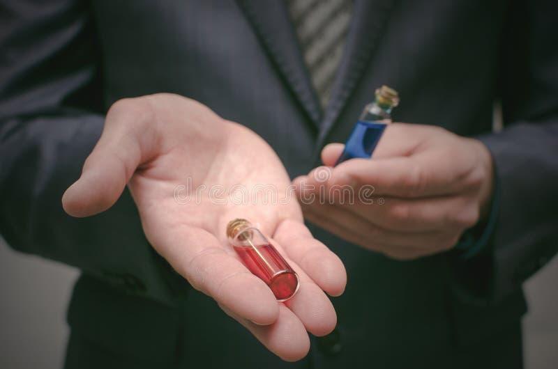 Liquido essenziale della pillola blu e rossa in mani dell'uomo di affari Giusta scelta dei medicinali immagine stock libera da diritti