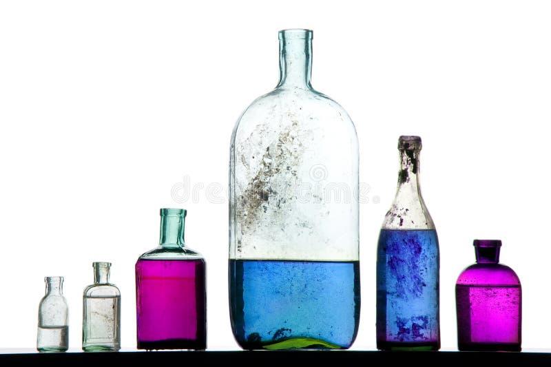 Liquido variopinto sulle bottiglie antiche fotografia stock