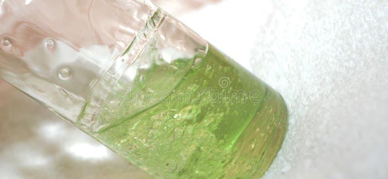Liquido verde in una bottiglia trasparente scossa immagine stock