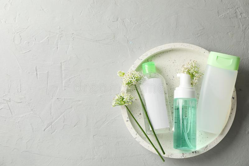 Liquids for body care in different bottles and allium flowers on white. Background stock images